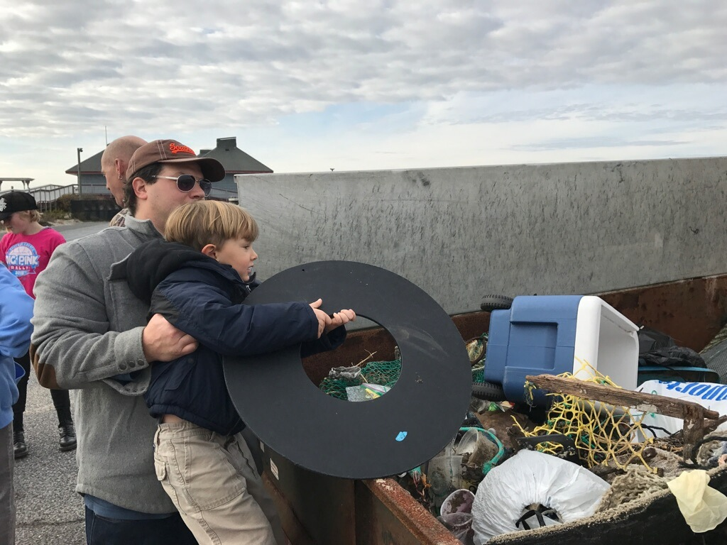 Parents lift their children to add their collected litter to the dumpster.
